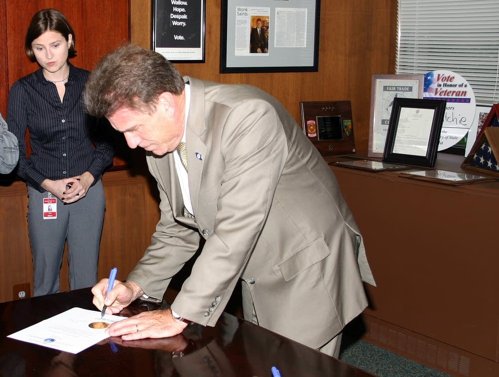 Mark Ritchie signs the election certificate