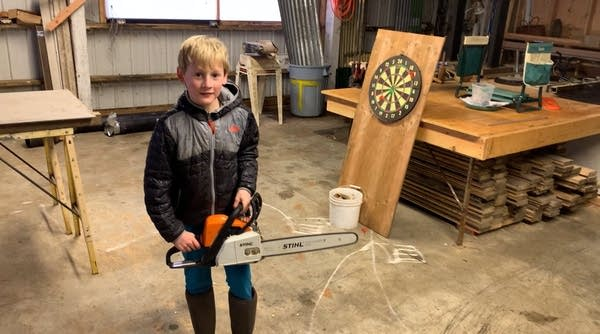 Young child (around 8 y.o.) holding chainsaw in garage or barn