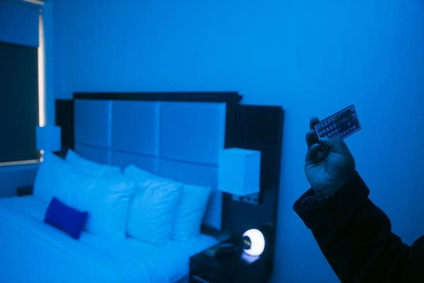 A remote changes a room's color inside luMINN hotel.