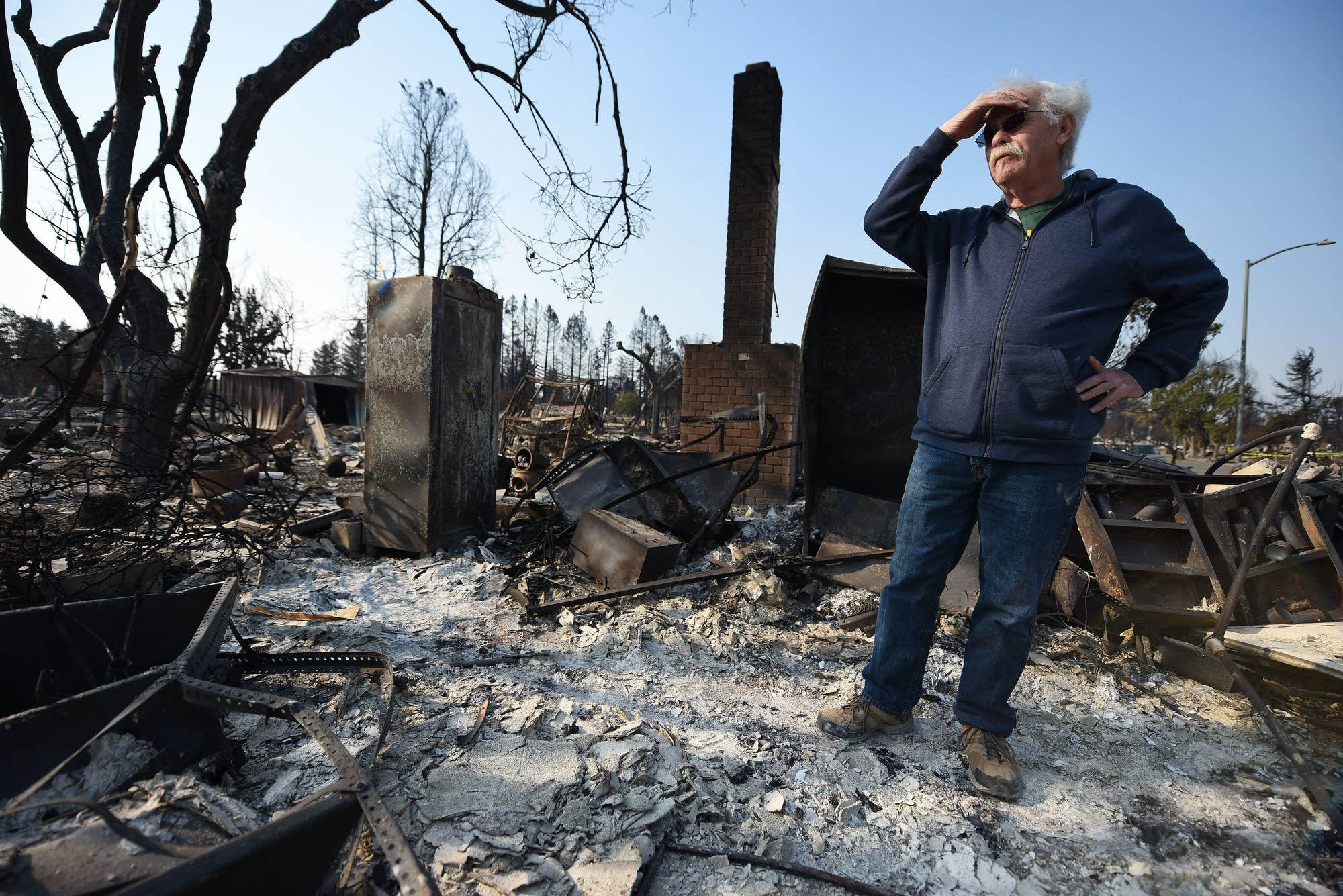 Homeowner Phil Rush looks at the remains of his home.