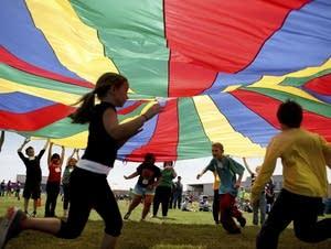 Third-graders run under a rainbow-colored tarp.