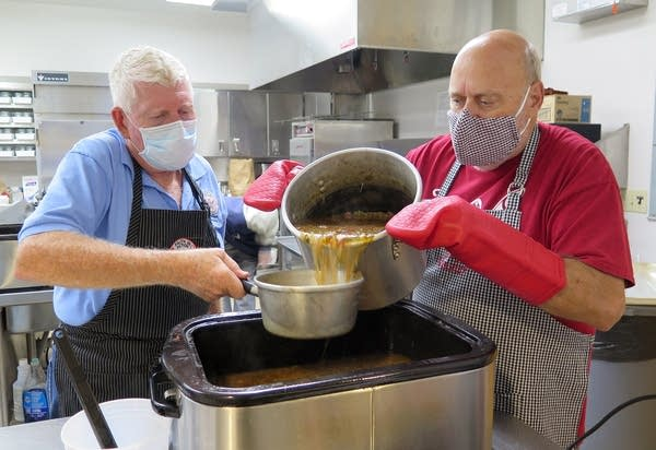 Two people stand in a kitchen and pour a stew in containers.